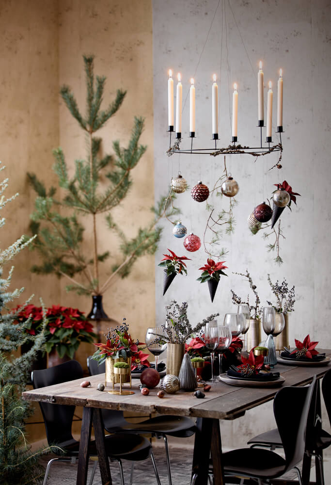 Ένα απλό ξύλινο τραπέζι αποχτά γιορτινό χαρακτήρα με λίγα φυτά και ανθισμένους βλαστούς από κόκκινο αλεξανδρινό.